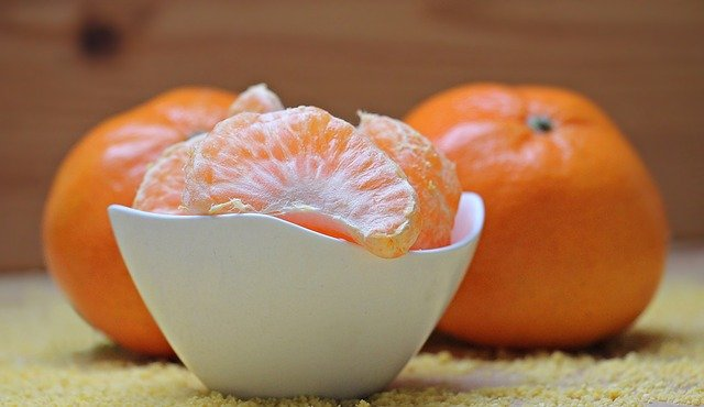 A close up of a bowl of oranges on a table